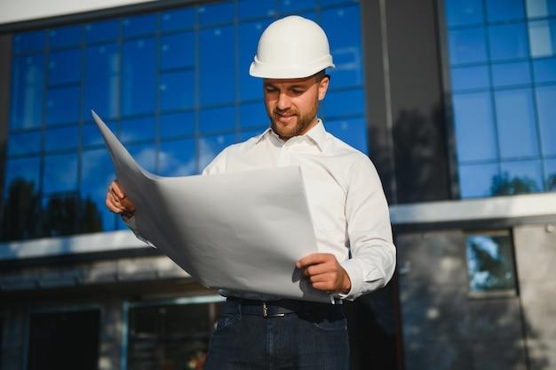 Ingegnere accanto alle gru edili. concept - grande progetto di costruzione. l'architetto dirige il processo di costruzione. disegni e tablet nelle mani.