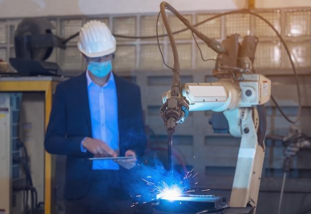 L'ingegnere controlla e controlla la macchina dei bracci robotici per l'automazione nella fabbrica intelligente industriale sul software del sistema di monitoraggio in tempo reale.