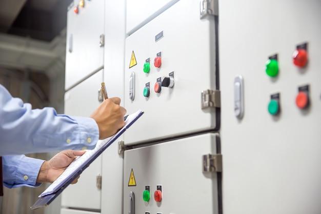 Tecnico che controlla il pulsante di avviamento dell'unità di trattamento aria ahu sul sistema del pannello di controllo.