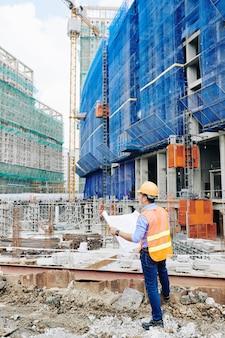 Ingegnere che controlla il progetto della costruzione