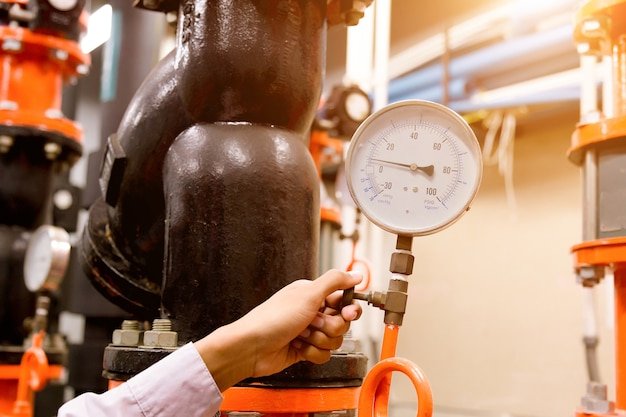 Ingegnere che controlla la pompa dell'acqua del condensatore e il manometro