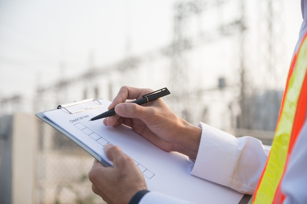 Ingegnere che controlla il sistema di sicurezza nella centrale elettrica, impianto ad alta tensione