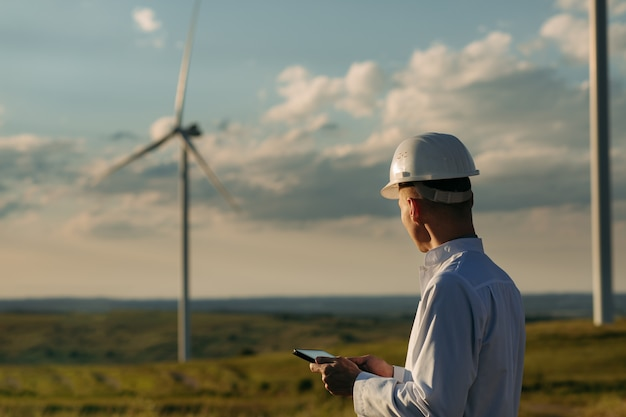 L'ingegnere controlla il sistema della turbina eolica con un tablet.