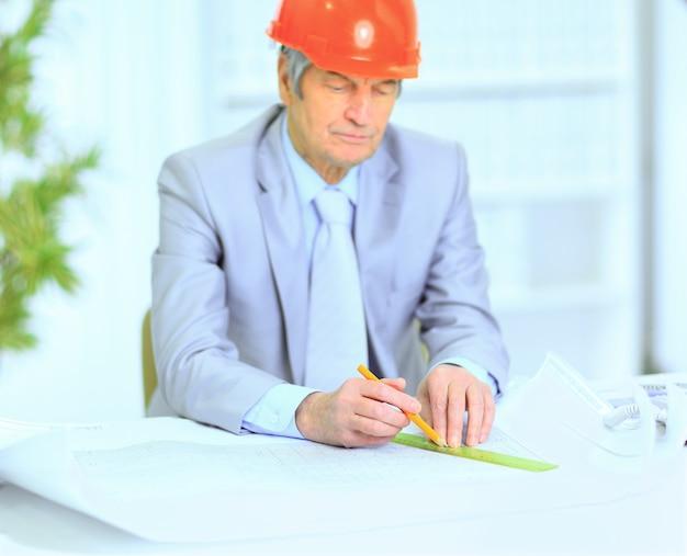 Ingegnere considerando i piani di disegno e li corregge.