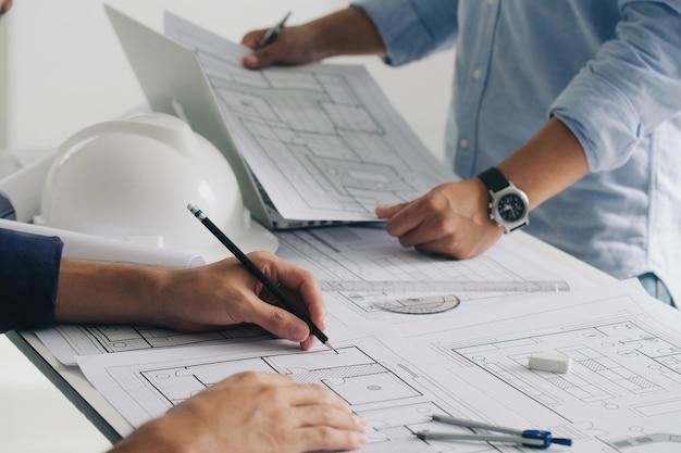 Costruzione di ingegneri e team di interni che discutono in ufficio e disegno di lavoro di un ingegnere