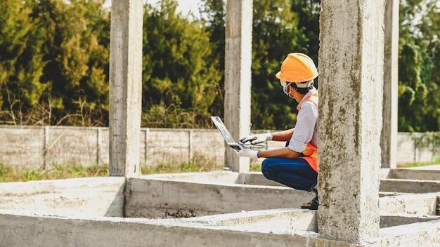 L'uomo dell'appaltatore dell'ingegnere usa il sito di costruzione dell'edificio del progetto dell'industria della sicurezza del lavoro del computer portatile