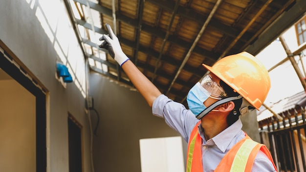 Ingegnere appaltatore uomo lavoro progetto settore sicurezza, controllare la progettazione del piano casa e indagare le dimensioni e la qualità nel sito di strutture di costruzione di edifici.