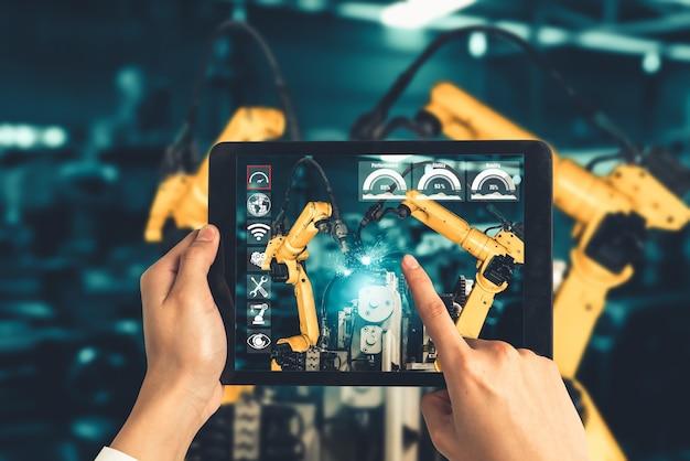 L'ingegnere controlla i bracci robotici mediante la tecnologia del settore della realtà aumentata