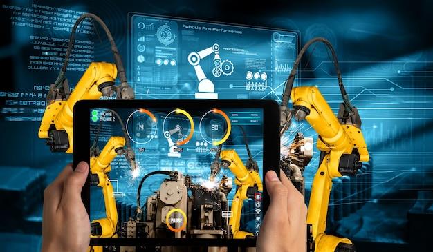 L'ingegnere controlla i bracci robotici con la tecnologia del settore della realtà aumentata