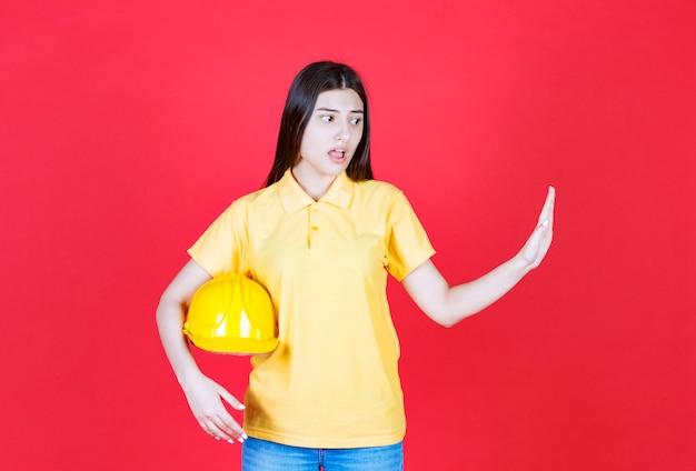 Ragazza ingegnere in codice di abbigliamento giallo che tiene un casco di sicurezza giallo e ferma qualcosa