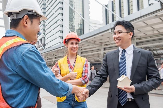 Accordo di stretta di mano del gruppo ingegnere con l'uomo d'affari per l'edilizia residenziale di progetto