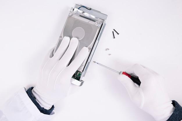 Mani di ingegnere riparazione disco rigido in laboratorio. supporto professionale per la manutenzione.