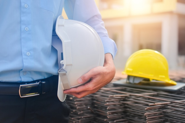 Ingegnere che tiene elmetto protettivo in piedi al lavoro di cantiere edile progetto architetto all'aperto