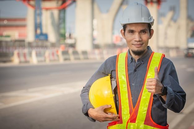 Ingegnere che tiene il casco sul posto costruzione di strade per lo sviluppo di moderni sistemi di trasporto, il lavoratore tecnico tiene al primo posto la sicurezza dell'elmetto