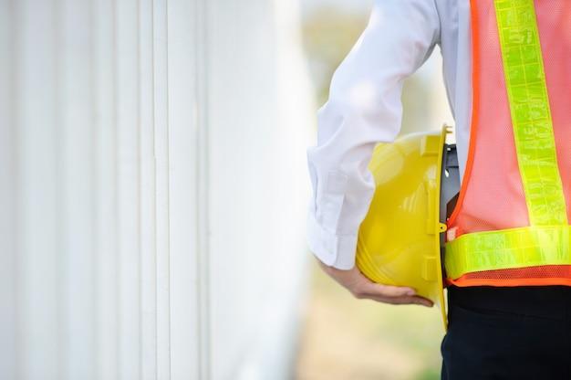 Ingegnere che tiene il fondo giallo della costruzione del casco di sicurezza del casco