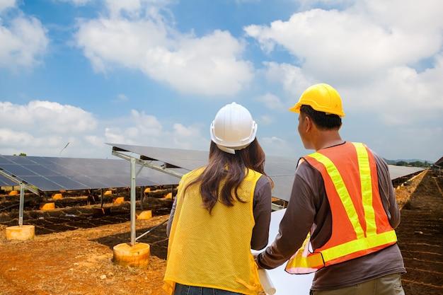 Ispettore ingegnere maschio e femmina che lavorano nella fattoria elettrica del pannello solare. concetto di energia verde del parco di celle fotovoltaiche