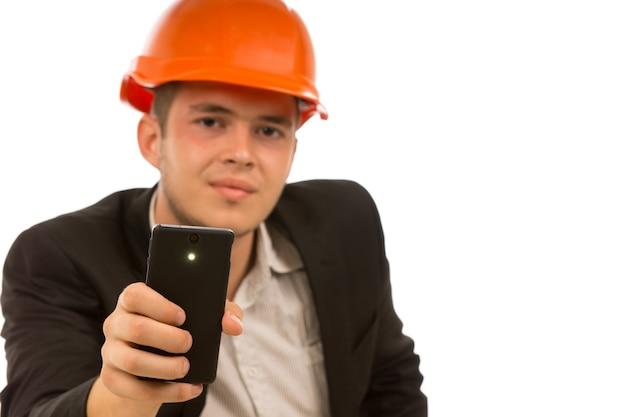 Ingegnere che guarda la telecamera mentre tiene il telefono