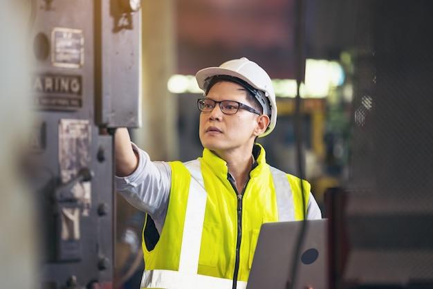 Uomo dell'ingegnere o tecnici che indossano mascherina chirurgica e utilizzando il computer portatile per il controllo