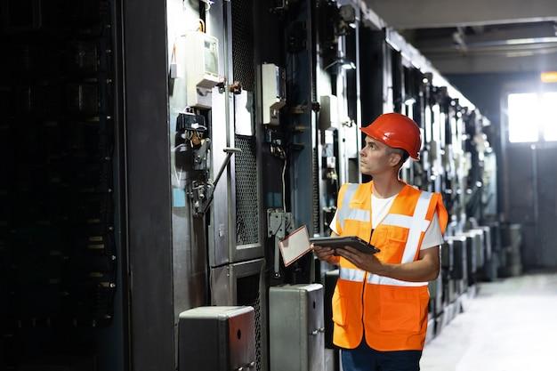 Ingegnere, uomo o lavoratore, che lavora in armadi di macchine per motori a energia elettrica di stazioni elettriche