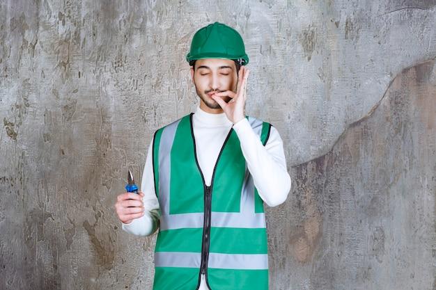 Uomo dell'ingegnere in uniforme gialla e casco che tiene le pinze blu per la riparazione e che mostra il segno positivo della mano.