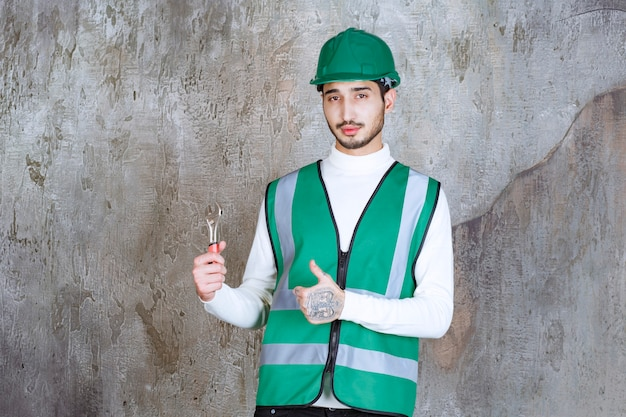 Uomo dell'ingegnere in uniforme gialla e casco che tiene una chiave metallica per la riparazione e che mostra il segno positivo della mano.