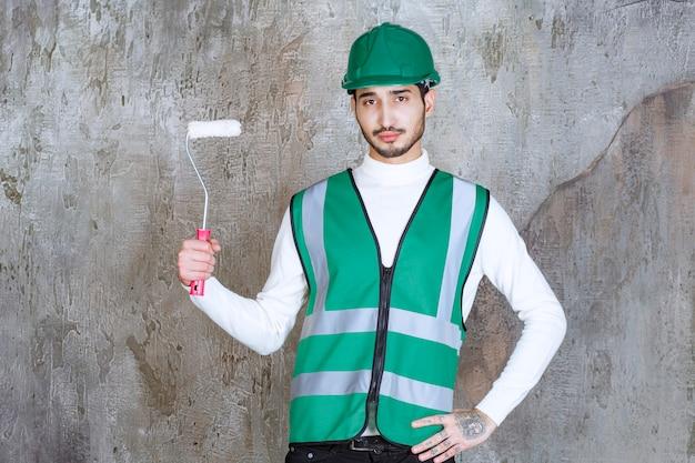 Uomo dell'ingegnere in uniforme gialla e casco che tiene un rullo di rifinitura per pittura murale.