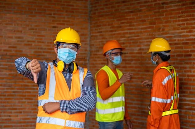 L'ingegnere non posa a mano un buon simbolo con una professione infelice a causa della situazione di malattia di covid-19.