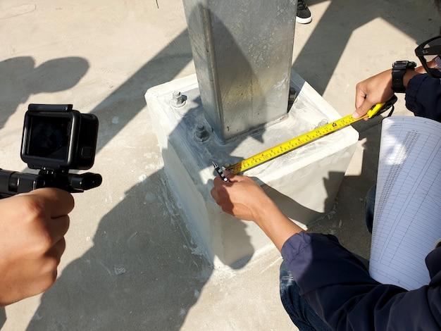 Ingegnere che ricontrolla la distanza dei bulloni di collegamento della piastra di base per la struttura in acciaio del posto auto coperto solare