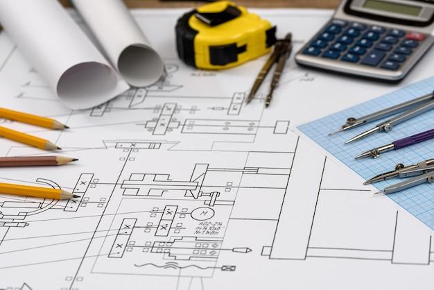 Primo piano del disegno dell'ingegnere con strumenti e calcolatrice