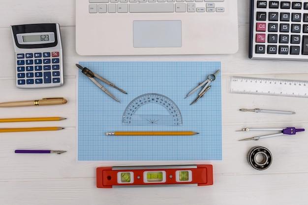 Posto di lavoro dell'ingegnere con carta millimetrata e attrezzatura da disegno