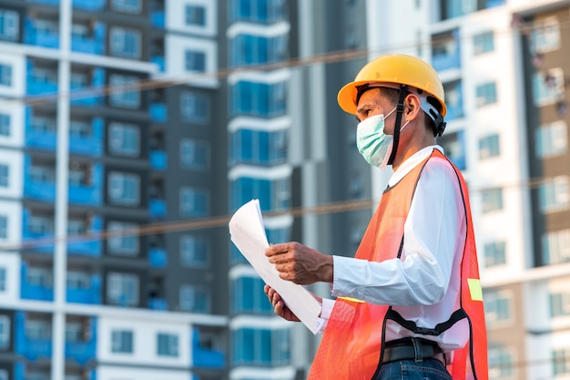 Ingegnere in piedi per ispezionare i piani di costruzione in cantiere