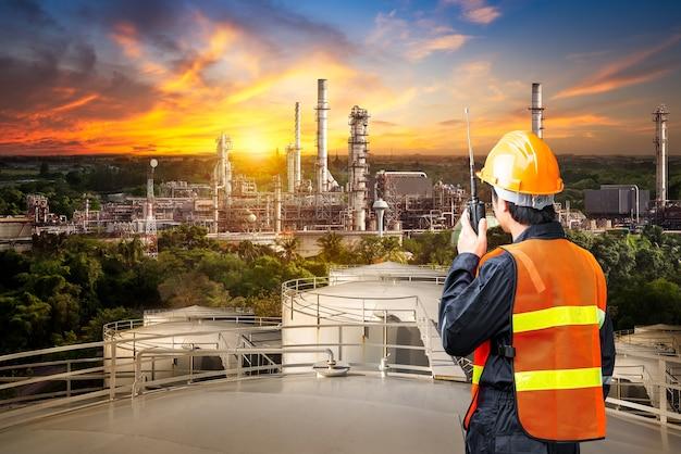 Indagine ingegneristica del raffinatore di petrolio e del lavoratore di controllo dalla radio portatile sul serbatoio di stoccaggio sullo sfondo del tramonto
