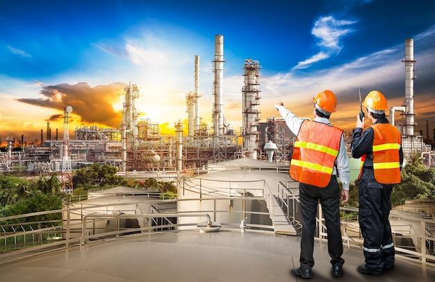 Indagine ingegneristica del raffinatore di petrolio e dell'addetto al controllo dalla radio portatile sul serbatoio di stoccaggio al tramonto