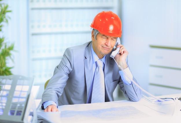 Ingegnere che parla al telefono dei piani del disegno.