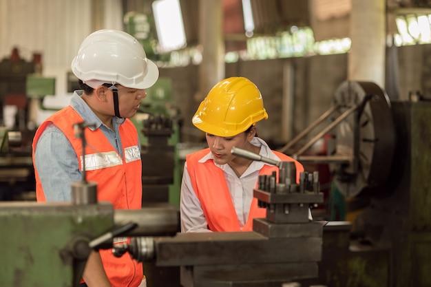 Il team di ingegneri maschi con donne che lavorano lavorano insieme nell'industria pesante insegnano e addestrano il funzionamento della macchina in fabbrica