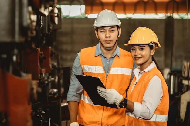 Il team di ingegneri che lavora con le donne lavora aiuta a sostenere insieme nell'industria pesante insegnare e addestrare il funzionamento della macchina in fabbrica