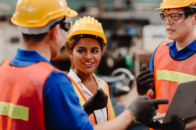 La corsa della miscela del gruppo dell'ingegnere che lavora insieme nell'industria pesante con la discussione del computer portatile, unisce il lavoro di squadra dell'ingegnere.