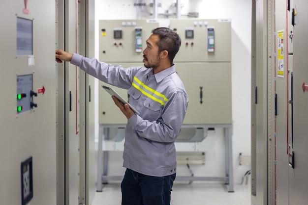 Ingegnere o tecnico che utilizza tablet per monitorare il processo, il business e il concetto di industria nella sala elettrica degli interruttori della piattaforma petrolifera e del gas o dell'impianto industriale.