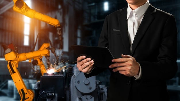 L'ingegnere utilizza un software robotico avanzato per controllare il braccio robotico industriale in fabbrica