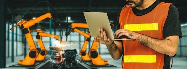 L'ingegnere utilizza un software robotico avanzato per controllare il braccio del robot industriale in fabbrica