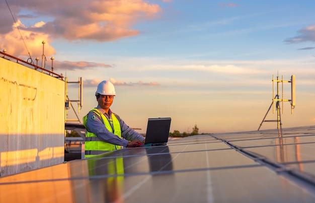 Ingegnere che utilizza laptop a pannelli solari sul tetto al tramonto, un ingegnere che lavora in una fattoria fotovoltaica. tecnologia ecologica per l'energia elettrica