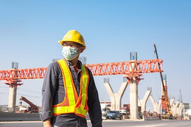 Maschera facciale di usura dell'ingegnere che lavora alla costruzione stradale del sito