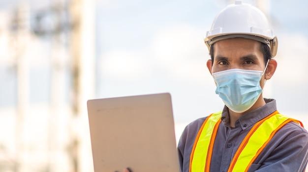 L'ingegnere indossa una maschera medica per proteggere il coronavirus covid19 e la tecnologia informatica all'aperto funzionante