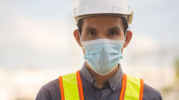 L'ingegnere indossa una maschera medica per proteggere il coronavirus covid19 e lavorare all'aperto