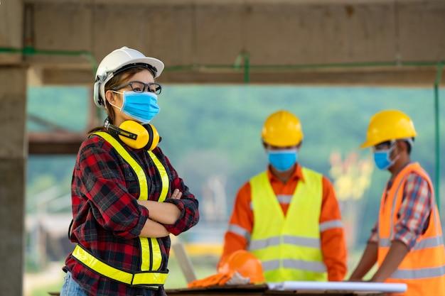 Ingegnere che indossa una maschera protettiva per proteggere contro covid-19 che lavora al cantiere, ingegnere meeting people brainstorming concept.