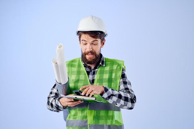 L'ingegnere in un casco bianco progetta uno sfondo blu professionale