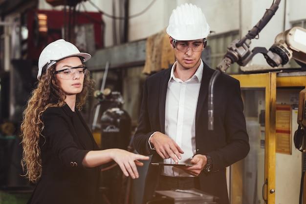 Ingegnere con tavoletta digitale che supervisiona il processo di produzione autonomo