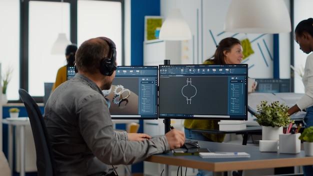 Ingegnere con auricolare che lavora sullo schermo del pc che mostra il software cad con componenti metallici di costruzione d...