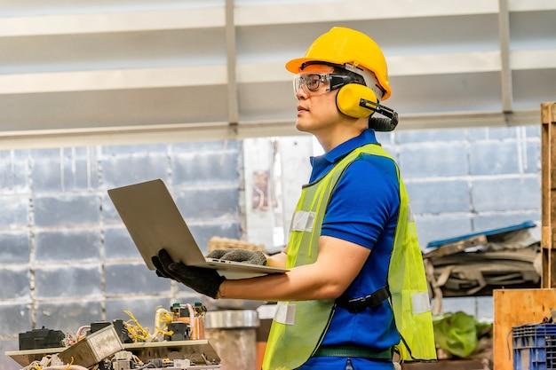 Ingegnere con casco di sicurezza che lavora in fabbrica