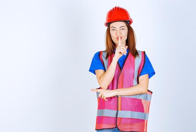 Donna ingegnere in uniforme e casco rosso che chiede silenzio.